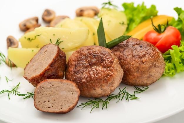 Costeletas caseiras com batatas e legumes em um fundo branco.