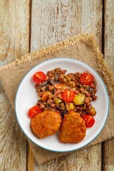 Costeletas de bacalhau com batata cozida e legumes em um prato em um guardanapo sobre a mesa.