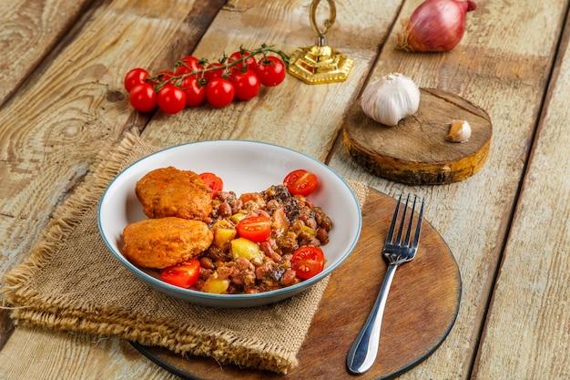 Costeletas de bacalhau com batata cozida e legumes num prato com ingredientes.