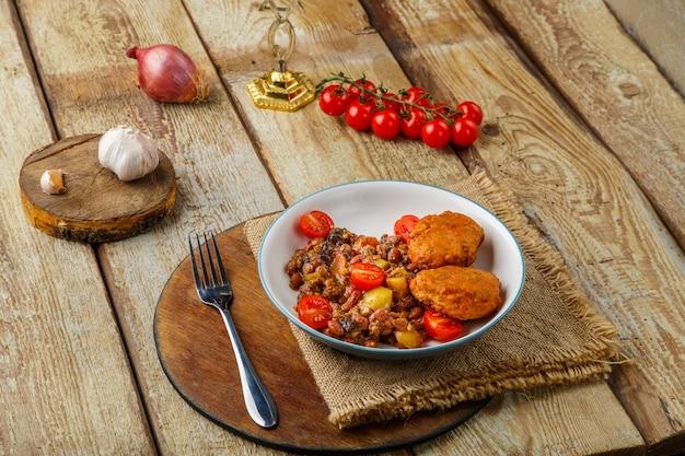 Costeletas de bacalhau com batatas e legumes em uma placa redonda perto dos ingredientes. foto horizontal