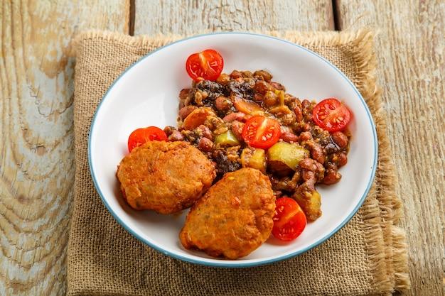 Costeletas de bacalhau com batatas e legumes num prato num guardanapo. foto horizontal