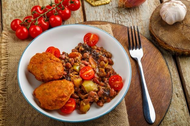 Costeletas de bacalhau com batatas e legumes numa base redonda junto aos ingredientes. foto horizontal