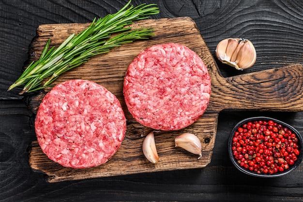 Costeletas de bife cru com carne bovina picada e alecrim em uma tábua de madeira com cutelo. fundo de madeira preto. vista do topo.
