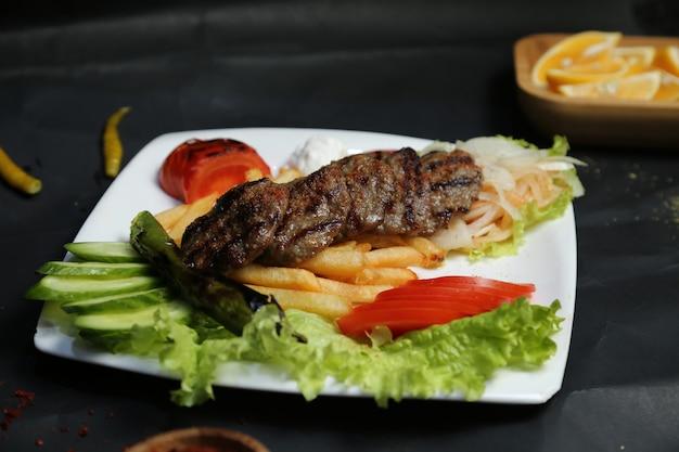 Costeletas de carne assada com batatas fritas e vegetais