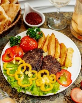 Costeletas de carne com batatas fritas e legumes