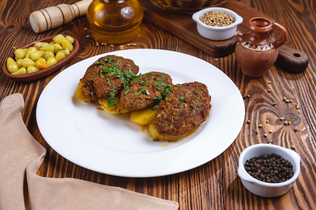 Costeletas de carne com temperos de batata verdes vista lateral