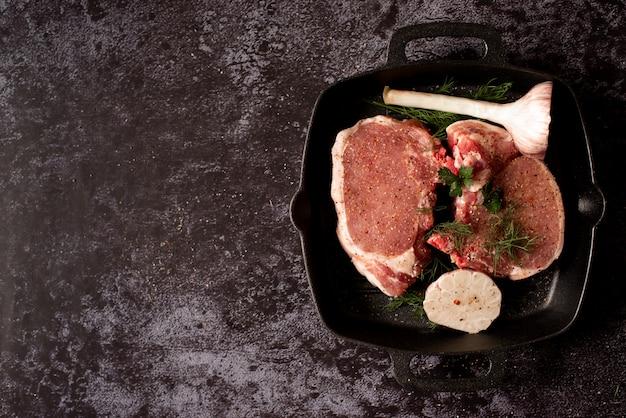 Costeletas de carne crua de cordeiro cru com alecrim e alho em panela de grelhar ferro preto
