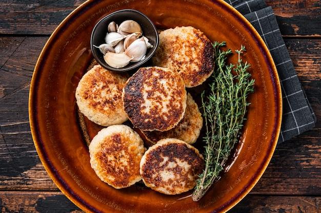 Costeletas de carne de porco e bovina fritas ou hambúrguer em prato rústico. fundo de madeira escuro. vista do topo.