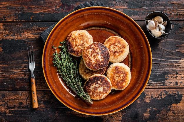 Costeletas de carne de porco e bovina fritas ou hambúrguer em prato rústico. mesa de madeira escura. vista do topo.