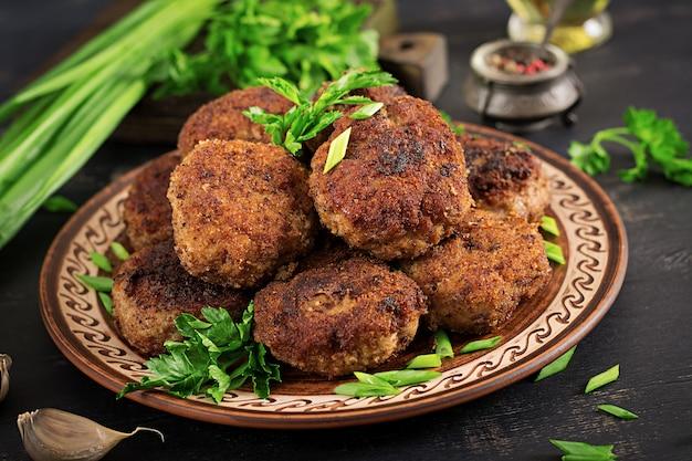 Costeletas de carne deliciosa suculenta em uma mesa escura. cozinha russa.