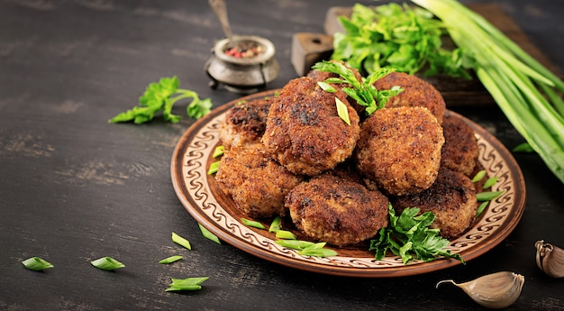 Costeletas de carne deliciosa suculenta em uma mesa escura