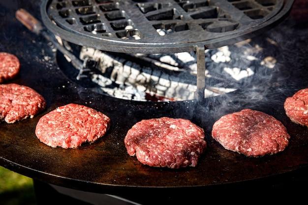 Costeletas de carne fresca em uma grelha de frigideira. cozinhando um hambúrguer grelhado