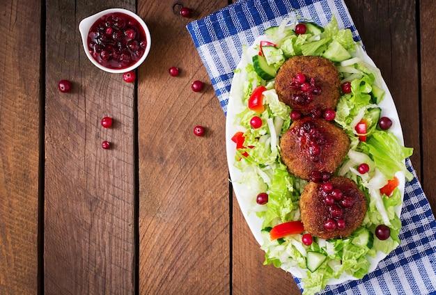 Costeletas de carne suculenta com molho de cranberry e salada em uma mesa de madeira em estilo rústico. vista do topo