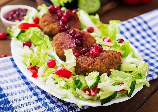 Costeletas de carne suculenta com molho de cranberry e salada em uma mesa de madeira em estilo rústico.