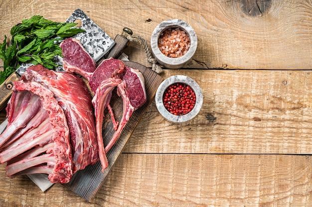 Costeletas de carneiro cru, costela e costela de carneiro em uma tábua de corte de açougueiro. fundo de madeira. vista do topo. copie o espaço.