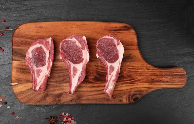 Costeletas de cordeiro cru, cortes de carne de carneiro ou costelas de ovelha no preto