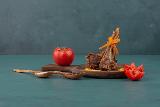 Costeletas de cordeiro grelhadas com vegetais fatiados na mesa azul.