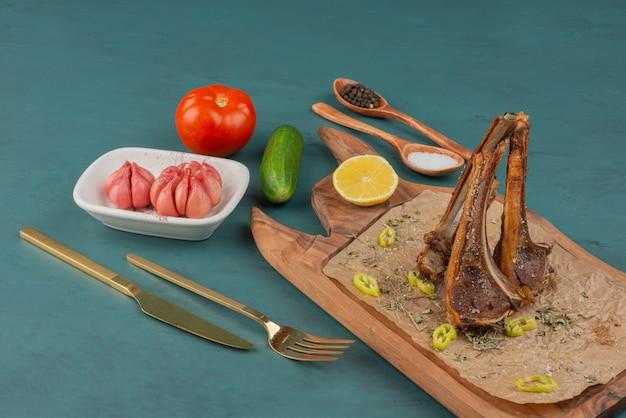 Costeletas de cordeiro grelhadas na placa de madeira com legumes.