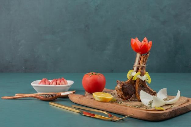 Costeletas de cordeiro grelhadas na tábua de madeira com legumes