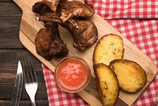 Costeletas de cordeiro plana leigos na placa de madeira com batatas e molho