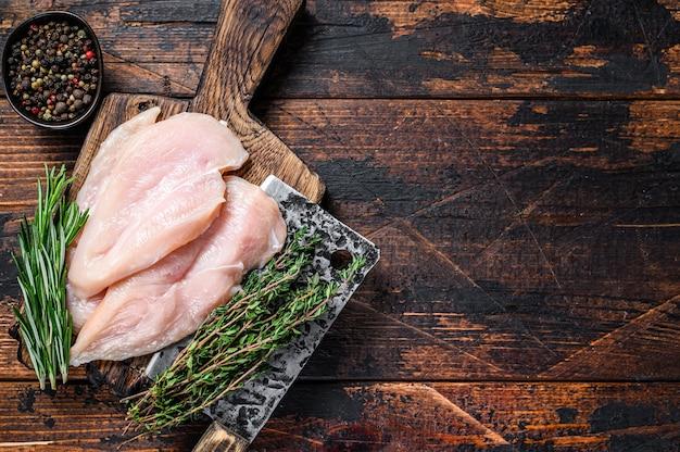Costeletas de filé de peito de frango cortado em fatias cruas em uma tábua de madeira com cutelo. fundo de madeira escuro. vista do topo. copie o espaço.