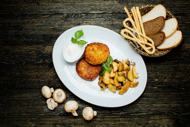 Costeletas de frango com batatas fritas e cogumelos
