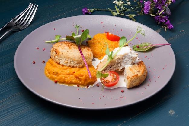 Costeletas de frango com purê de abóbora com tomate e microgreens