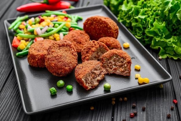 Costeletas de frango na massa com risoto e vegetais, em superfície preta