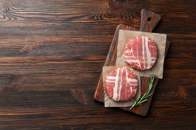 Costeletas de hambúrguer cru com alecrim na tábua e mesa de madeira