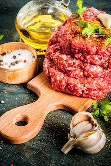 Costeletas de hambúrguer cru com sal, pimenta, óleo, ervas e especiarias
