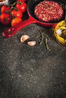 Costeletas de hambúrguer de carne de bovino orgânico cru com especiarias, tomilho, tomate, azeite na frigideira em preto, copyspace vista superior