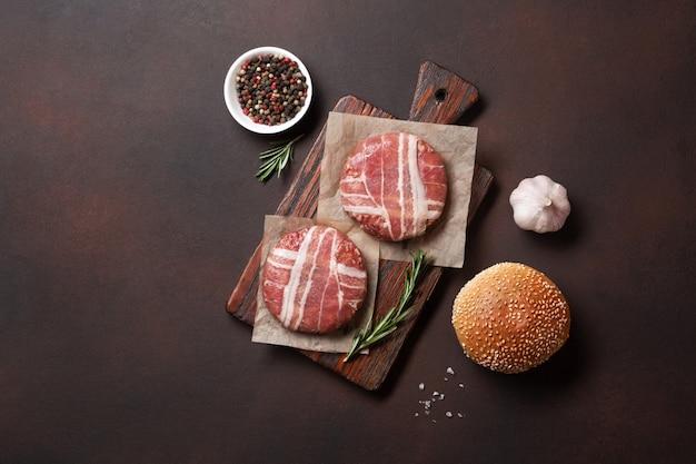 Costeletas de hambúrguer ingredientes crus, alface, pão e cebola em fundo enferrujado