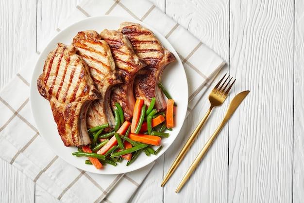 Costeletas de lombo de porco grelhadas servidas com salada de feijão verde e cenoura em um prato branco sobre uma mesa de madeira com garfo e faca de ouro, vista horizontal, flatlay