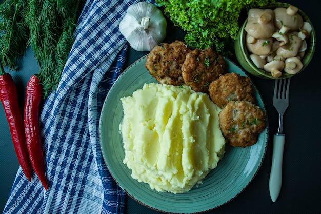 Costeletas de porco com purê de batatas, verduras e legumes frescos