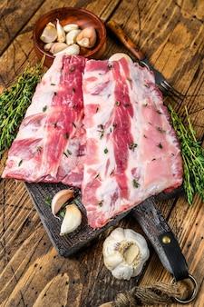Costeletas de porco crua fresca com tomilho e alho na tábua. fundo de madeira. vista do topo.