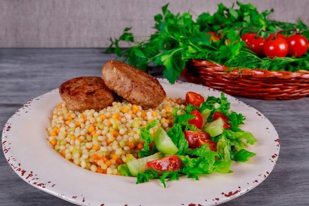 Costeletas de porco, cuscuz com legumes e rúcula.