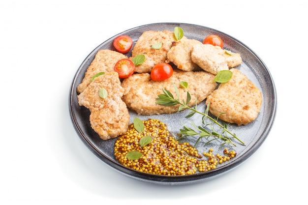 Costeletas de porco frito com tomates e ervas em um prato de cerâmico cinza isolado no fundo branco. vista lateral.