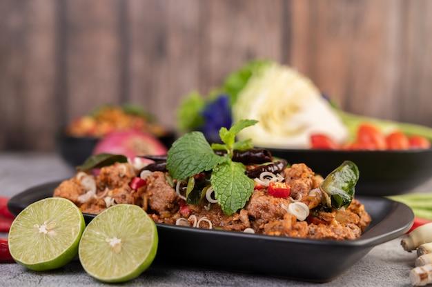 Costeletas de porco picante em um prato preto, composto por limões pimentão e acompanhamentos