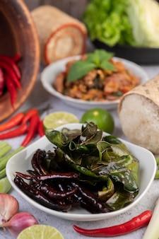 Costeletas de porco picantes em um prato branco que consiste em limões, pimentões e acompanhamentos. foco seletivo.