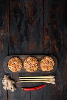 Costeletas de salmão asiático crus, na velha mesa de madeira