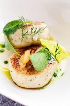 Costeletas de salmão e bacalhau com espinafre e caviar de lúcio com molho branco em restaurante que serve. keto, paleo, comida dietmap fodmap. fechar-se.