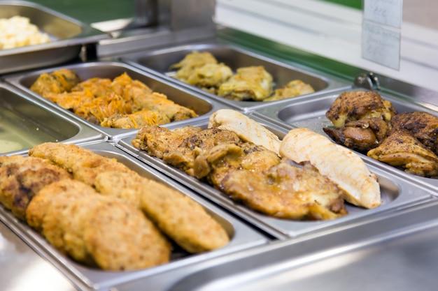 Costeletas e pratos de carne em buffet em placas de metal. foco seletivo