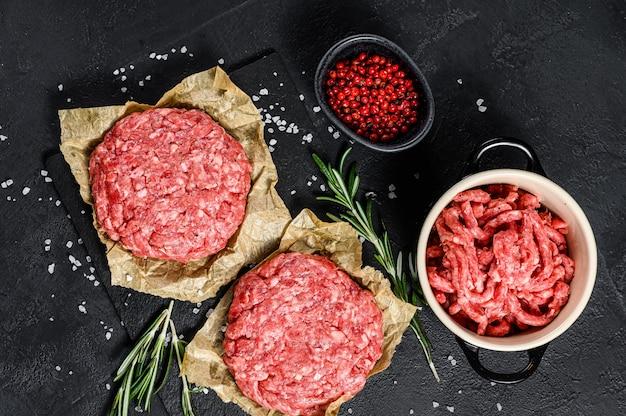 Costeletas e temperos crus do bife do hamburguer. fazenda de carne orgânica. vista do topo