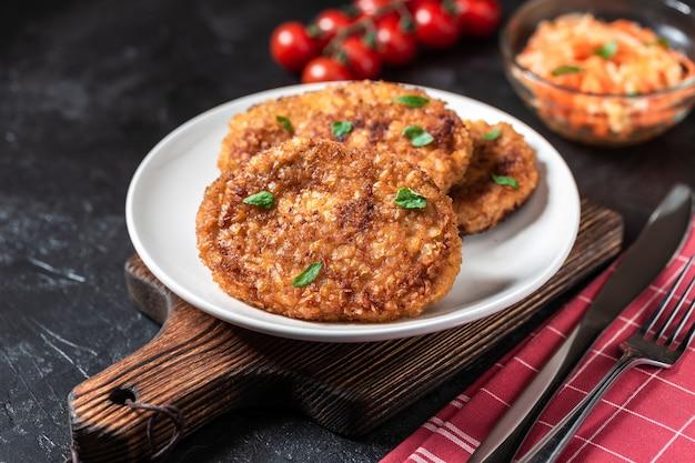 Costeletas estão em um prato branco. costeletas de frango estão entre os legumes em uma mesa de pedra preta.