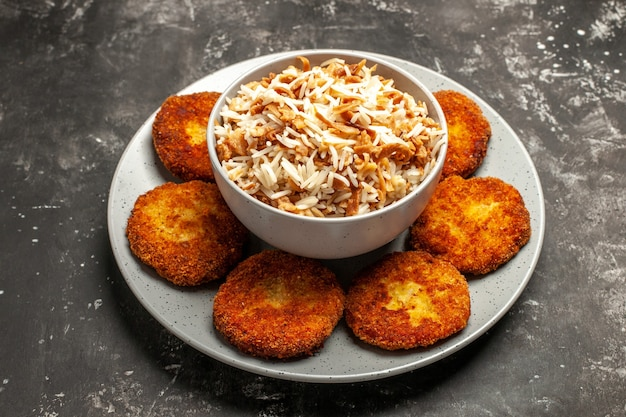 Costeletas fritas com arroz cozido em um prato de superfície escura com carne de rissole