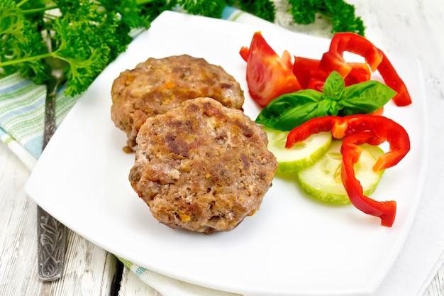 Costeletas recheadas com espinafre e ovos em um prato, uma salada de tomate, pepino e pimenta, manjericão e salsa em um fundo de tábua de madeira