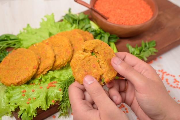 Costeletas vegetarianas de lentilhas e cenouras em uma placa de madeira com legumes e ervas.