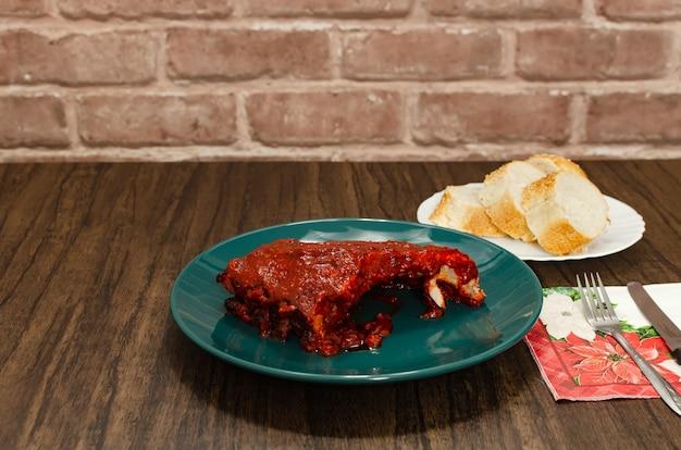 Costelinha assada marinada com molho barbecue na mesa de madeira