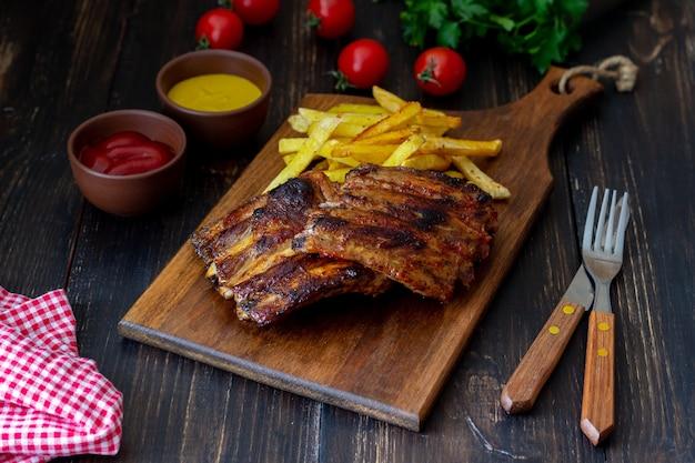 Costelinha de churrasco com batata frita. cozinha americana. grade. bbq.