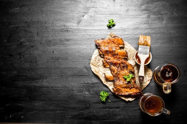 Costelinha de porco grelhada com cerveja e molho no quadro de giz preto
